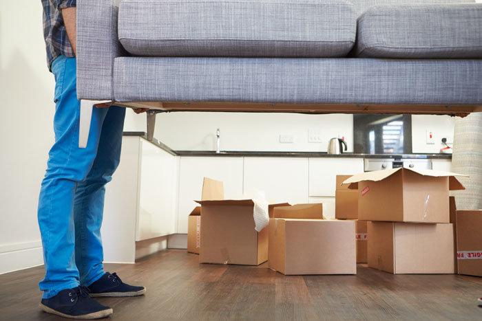 Грузчики несут диван - переезд на новую квартиру